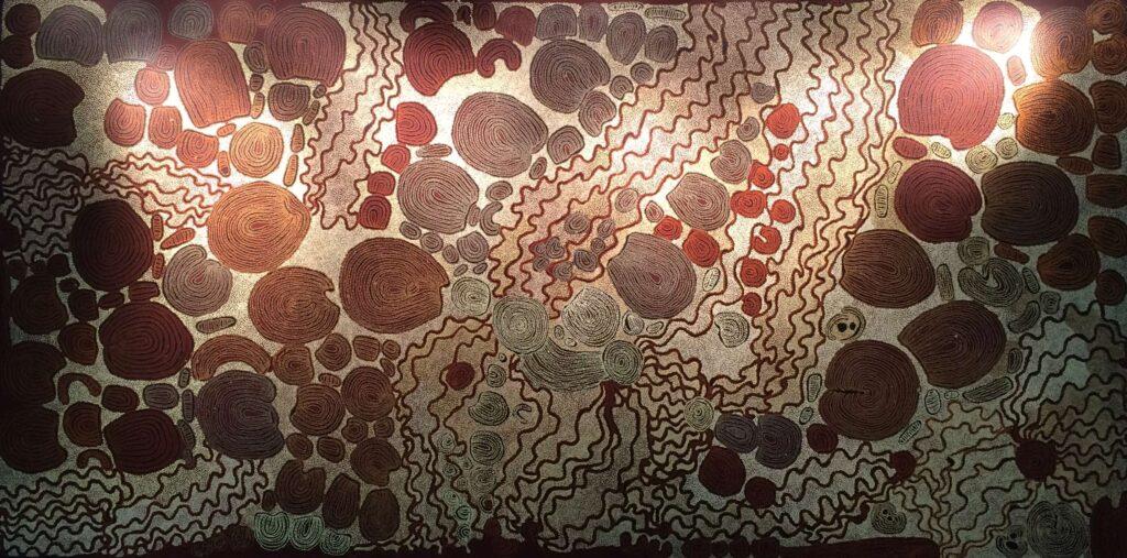 Fotografia przedstawia duży obraz, który może przywoływać skojarzenia z kamieniami, pomiędzy którymi przepływa woda. Powierzchnię obrazu pokrywają, skupione w grupy,  brązowe okręgi o rożnej wielkości i mniej lub bardziej regularnej formie. Każdy z okręgów pokryty jest wewnątrz regularnie, koncentrycznie naniesionymi białymi kropeczkami. Grupy kół rozdzielone są falistymi brązowymi liniami. Przestrzenie pomiędzy liniami i kołami, na całej powierzchni obrazu, szczelnie wypełniają niezliczone ilości drobnych białych kropek, spod których delikatnie przebija ciepłe, brązowe tło obrazu.