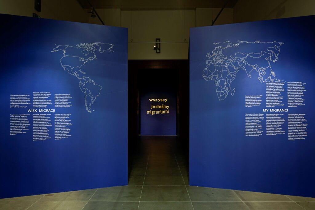 """Fotografia przedstawia przedsionek Sali Wystaw będący wprowadzeniem do wystawy. Całe pomieszczenie zostało zabudowane. Na pierwszym planie znajdują się dwie duże, ciemnoniebieskie ściany działowe ustawione frontem do widza. Na nich zawieszona została biała, konturowa mapa świata i teksty wprowadzające do wystawy. Po prawej stronie umieszczona jest Europa, Afryka i Australia oraz tekst komentarza zatytułowany """"My migranci"""", a po lewej obie Ameryki i tekst zatytułowany """"Wiek migracji"""". Na mapie czerwonymi kropkami zaznaczone są miejsca migracji oraz − białymi kropkami − morski szlak podróży emigrantów, o których opowiada wystawa. Obie ściany, jak i umieszczoną na nich mapę świata, rozdziela długi korytarz prowadzący do głównej sali wystawowej, której widok przesłania ściana działowa, również w ciemnoniebieskim kolorze ze złotym, dużym i migoczącym odbitym światłem napisem """"wszyscy jesteśmy migrantami""""."""