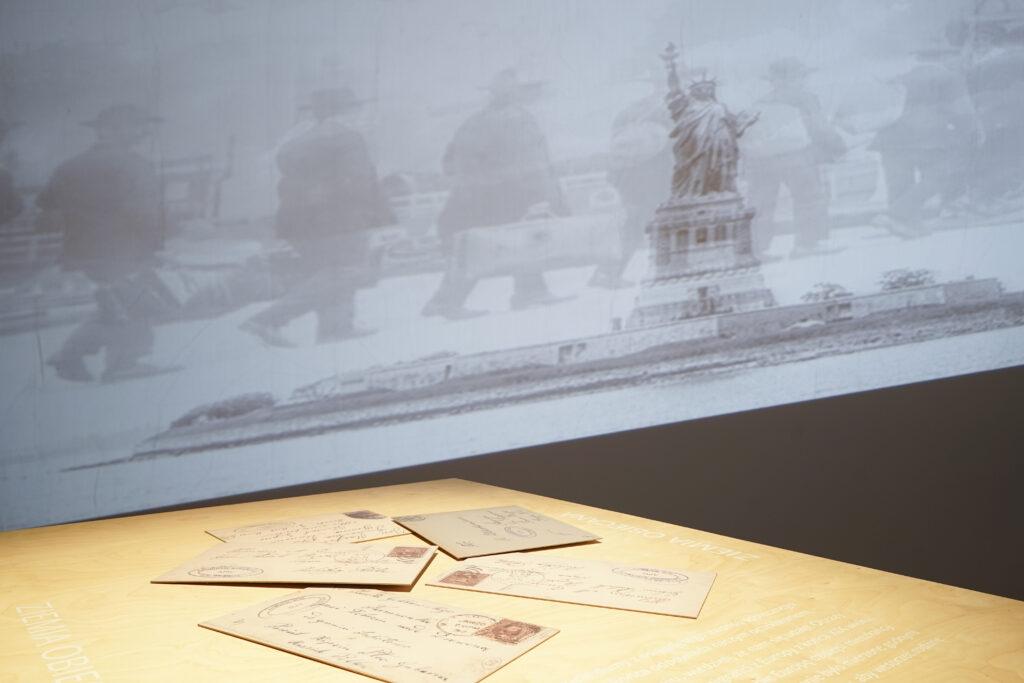 Fotografia przedstawia zbliżenie fragmentu ekspozycji wystawy. Na pierwszym planie znajduje się drewniany blat gabloty, na którym leżą rozrzucone i powiększone zaadresowane koperty starych listów. W tle na ścianie wyświetla się historyczna fotografia Statuy Wolności, na obraz której nakłada się widok idących emigrantów z walizkami.