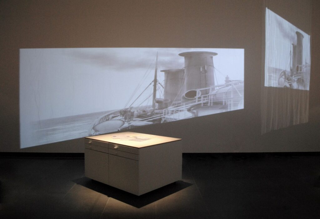 Fotografia przedstawia zbliżenie fragmentu ekspozycji wystawy. Na pierwszym planie stoi pojedyncza gablota. Na jej dłuższych bokach znajdują się po cztery szuflady, w układzie po dwie obok siebie, w których ukryta została wystawa. Na drewnianym blacie leżą powiększone zaadresowane koperty starych listów. W tle na ścianie z projektora wyświetlana jest stara fotografia przedstawiająca widok z pokładu transoceanicznego parowca.