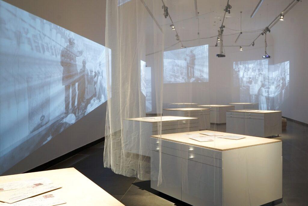 Fotografia przedstawia ogólny widok wystawy. W białej i dość ascetycznej sali wystawowej rozstawione są białe, prostokątne, surowe i proste gabloty nakryte drewnianymi blatami. Przypominają samotne wyspy nieregularnie rozrzucone w bezkresie oceanu. Na dłuższych bokach gablot znajdują się po cztery szuflady, w układzie po dwie obok siebie, w których ukryta została wystawa. Na blatach leżą powiększone zaadresowane koperty starych listów. Przestrzeń przecinają tiulowe zasłony, przez które przenika obraz rzucany przez projektory w postaci starych fotografii emigrantów stojących na portowym nabrzeżu. Obraz powiela się i załamuje nieregularnie na ścianach pomieszczenia. W głębi sali dwie osoby pochylone nad otwartymi szufladami czytają i przeglądają ich zawartość.