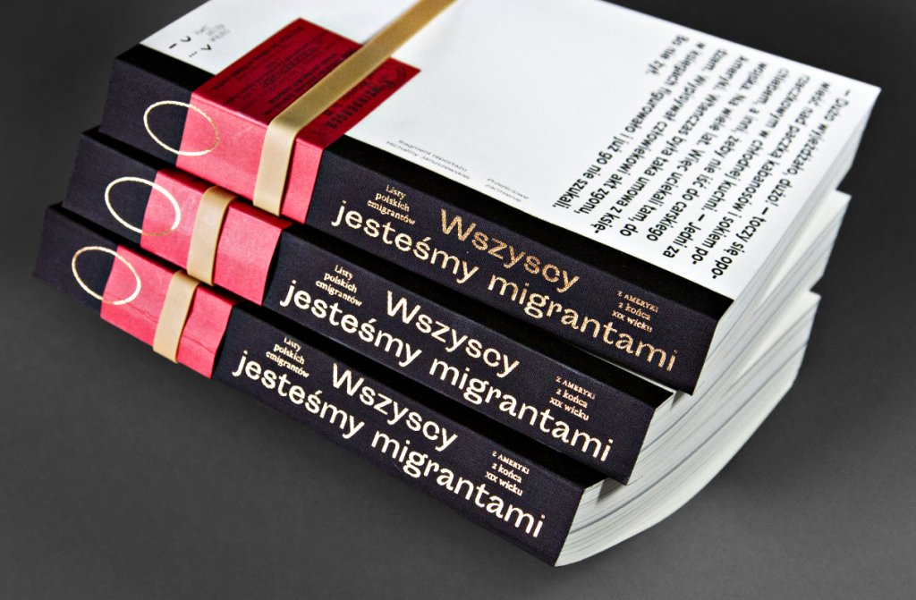 """Fotografia przedstawia trzy książki leżące jedna na drugiej na czarnym blacie stołu. Książki nie mają okładki, przewiązane są gumką i wyglądają jak zbiór notatek, archiwalnych materiałów. Biały, papierowy tył publikacji, z umieszczonym na nim fragmentem tekstu, kontrastuje z czerwienią nawiniętego na brzeg książki kartoniku, będącego kopią druku reklamowego starego biura podróży. Książki ułożone są grzbietem w stronę widza. Grzbiet wykonany jest z czarnego płótna, w którym wytłoczone zostały duże złote litery układające się w napis: """"Wszyscy jesteśmy migrantami"""" i mniejsze tworzące napis: """"Listy polskich emigrantów z Ameryki z końca XIX wieku""""."""