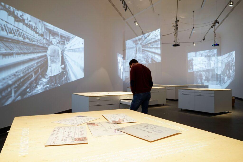 """Fotografia przedstawia zbliżenie fragmentu ekspozycji wystawy. Na pierwszym planie znajduje się obszerny drewniany blat, na którym leżą rozrzucone i powiększone zaadresowane koperty starych listów. Na blacie wylepiony został, też białymi literami, tytuł """"Droga cierniowa"""" i krótki tekst komentarza. W tle sali znajdują się rozstawione białe, prostokątne, surowe i proste gabloty nakryte drewnianymi blatami. Przypominają samotne wyspy nieregularnie rozrzucone w bezkresie oceanu. Na dłuższych bokach gablot znajdują się po cztery szuflady, w układzie po dwie obok siebie, w których ukryta została wystawa. Na blatach leżą powiększone zaadresowane koperty starych listów. Przestrzeń przecinają tiulowe zasłony, przez które przenika obraz rzucany przez projektory w postaci starych fotografii emigrantów − portret dziewczynki na tle maszyn włókienniczych. Obraz powiela się i załamuje nieregularnie na ścianach pomieszczenia. W głębi sali mężczyzna zwrócony do nas plecami pochyla się nad otwartą szufladą, czytając i przeglądając jej zawartość."""