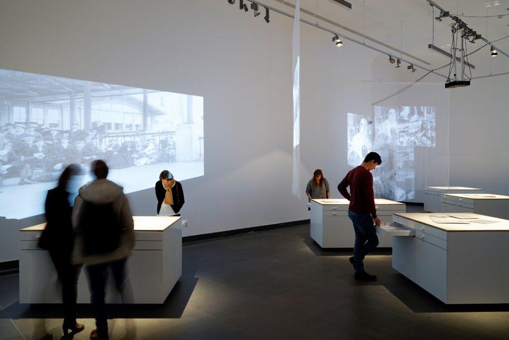 Fotografia przedstawia ogólny widok wystawy. W białej i dość ascetycznej sali wystawowej rozstawione są białe, prostokątne, surowe i proste gabloty nakryte drewnianymi blatami. Przypominają samotne wyspy nieregularnie rozrzucone w bezkresie oceanu. Na dłuższych bokach gablot znajdują się po cztery szuflady, w układzie po dwie obok siebie, w których ukryta została wystawa. Na blatach leżą powiększone zaadresowane koperty starych listów. Przestrzeń przecinają tiulowe zasłony, przez które przenika obraz rzucany przez projektory w postaci starych fotografii emigrantów stojących na portowym nabrzeżu. Obraz powiela się i załamuje nieregularnie na ścianach pomieszczenia. W głębi sali osoby pochylone nad otwartymi szufladami czytają i przeglądają ich zawartość.