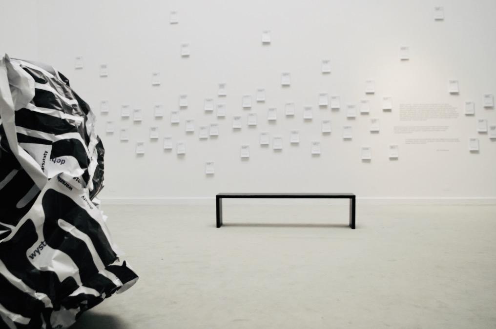 Fotografia przedstawia ścianę w przedsionku Sali Wystaw. Na całej długości ściany zawieszone są nieregularnie niewielkie papierowe ulotki zawierające komentarz prof. J. Bralczyka do wybranych zdań, które zwiedzający wystawę mogli zabrać ze sobą.