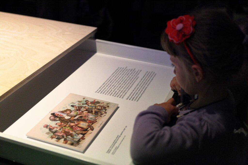 Fotografia przedstawia fragment ekspozycji wystawy. Na pierwszym planie znajduje się w zbliżeniu otwarta szuflada, do której zagląda mała dziewczynka. Czyta z zaciekawieniem znajdujący się w szufladzie fragment tekstu oraz spogląda na kolorową grafikę – karykaturę ze starej amerykańskiej gazety przedstawiającej emigrantów.
