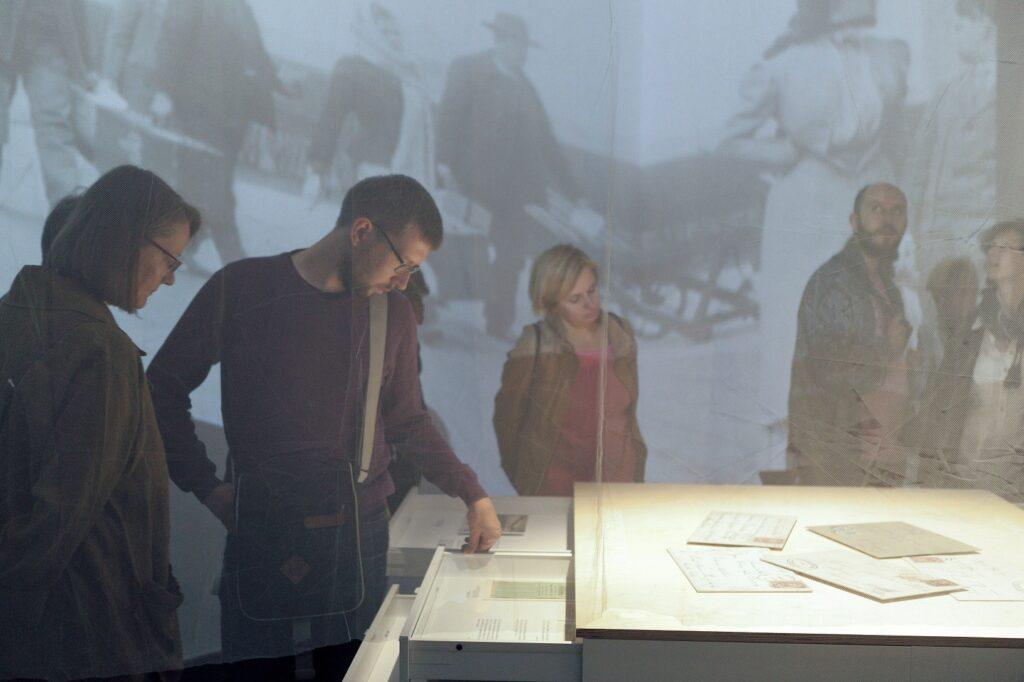 Fotografia wykonana została przez tiulową zasłonę i przedstawia zbliżenie fragmentu ekspozycji wystawy. Na pierwszym planie znajduje się ustawiona bokiem gablota z otwartymi szufladami, nad którymi stoją pochyleni kobieta i mężczyzna. Czytają ich zawartość. W tle zwiedzający spoglądają do innych szuflad oraz patrzą na projekcje pojawiające się na ścianach i przedstawiające emigrantów z bagażami w porcie, wysiadających z okrętu.