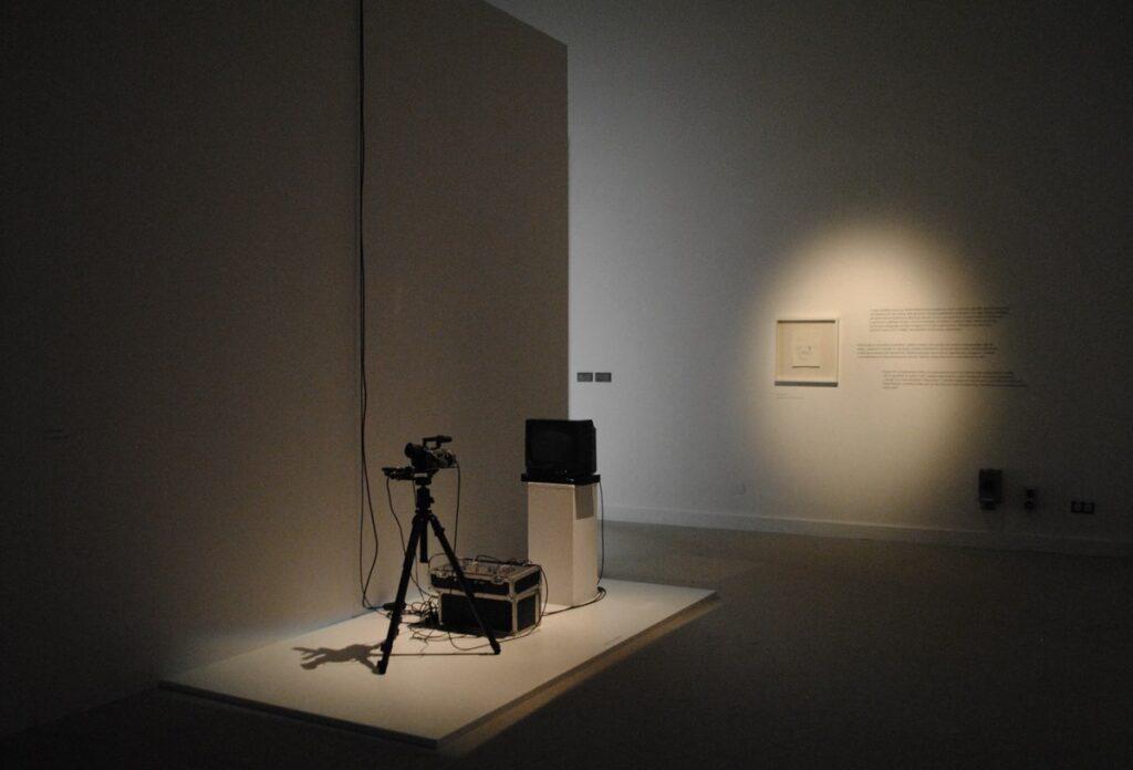 Fotografia przedstawia fragment instalacji multimedialnej ustawionej w głównej sali wystawowej. Instalacja znajduje się po lewej stronie fotografii i dostawiona jest do ściany na niskim białym podeście. Składa się ona z cyfrowej kamery ustawionej na trójnogu, skierowanej obiektywem w stronę stojącego naprzeciw niej telewizora. W tle znajduje się oświetlona punktowym światłem biała ściana, z płaszczyzny której wydobywa się obrazek oprawiony w białą ramę oraz tekst komentarza opisujący sposób działania projekcji.