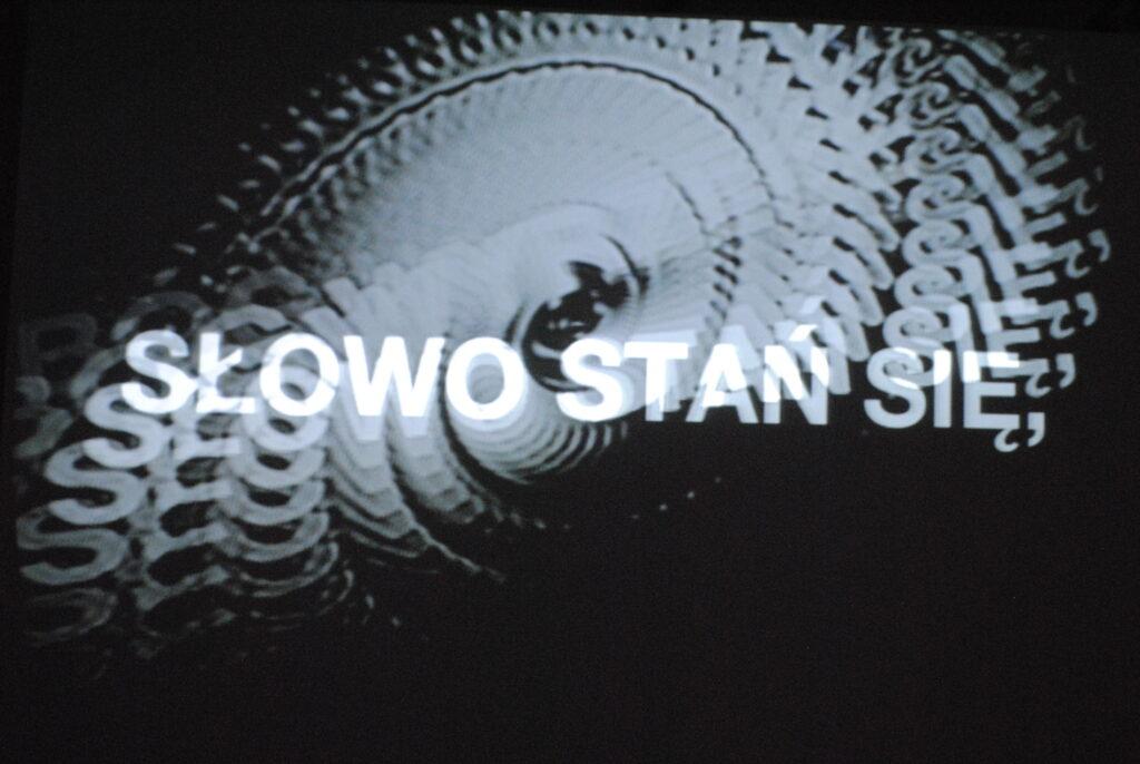 """Fotografia przedstawia fragment ekranu z projekcją z wystawy """"#1050"""" tworzonej poprzez zniekształcanie medium obrazu analogowego. Na czarnym tle biały obraz budują jakby ślady liter i słów poddanych ruchowi wirowemu."""