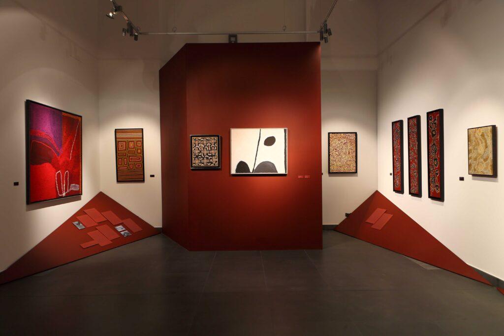 Ekspozycja w pierwszej sali wystawowej. Kolorystka pomieszczenia, oświetlenie oraz forma aranżacji charakterem nawiązują do australijskiego krajobrazu oraz motywów widocznych na obrazach. Duża brązowa ściana działowa, niczym skalna ściana, przysłaniająca przejście do głównej sali wystawowej, stanowi centralny element  dominujący w pomieszczeniu. Na jej płaszczyźnie oraz odcinających się białych płaszczyznach ścian pomieszczenia zawieszone są równo, wyśrodkowane względem siebie obrazy. Miejsca styku  ścian z podłogą przysłaniają ułożone po skosie brązowe trójkrotne panele, przypominające piaskowe wzniesienia, na których umieszczone są teksty komentarzy i czarnobiałe fotografie archiwalne przedstawiające malarzy aborygeńskich podczas pracy.