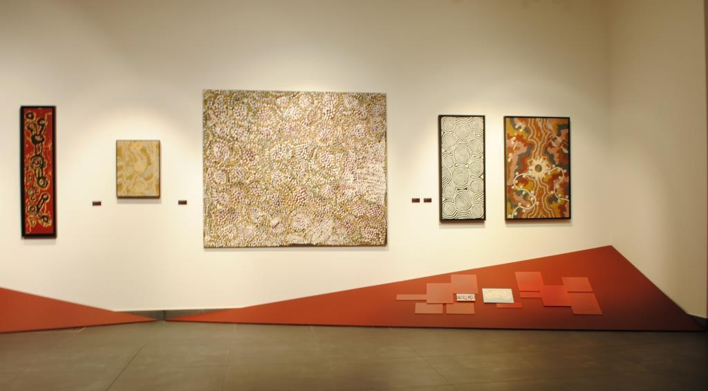 Ściana wystawowa w pierwszej sali wystawowej. Na jej białej płaszczyźnie zawieszone są równo, wyśrodkowane względem siebie obrazy. Miejsce styku ścian z podłogą przysłaniają ułożone po skosie brązowe trójkrotne panele, przypominające piaskowe wzniesienia, na których umieszczone zostały teksty komentarzy i czarno-białe fotografie archiwalne przedstawiające malarzy aborygeńskich podczas pracy.