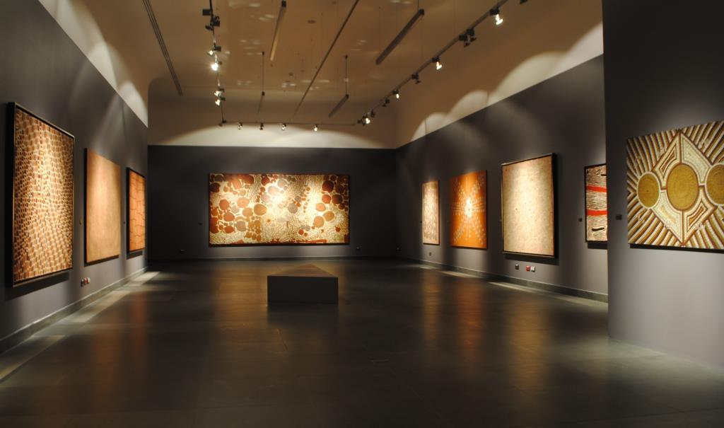 Panorama głównej sali wystawy. Ciemnoszara kolorystyka ścian łącząca się z ciemnoszarym kolorem podłogi potęgują efekt mroczności, przywołując klimat jaskini. Na ścianach wiszą, jeden obok drugiego, dużych rozmiarów obrazy. Punktowe oświetlenie wydobywa geometryczne, abstrakcyjne wzory na płaszczyźnie obrazów, mieniące się ziemistymi kolorami brązów oraz pomarańczy.