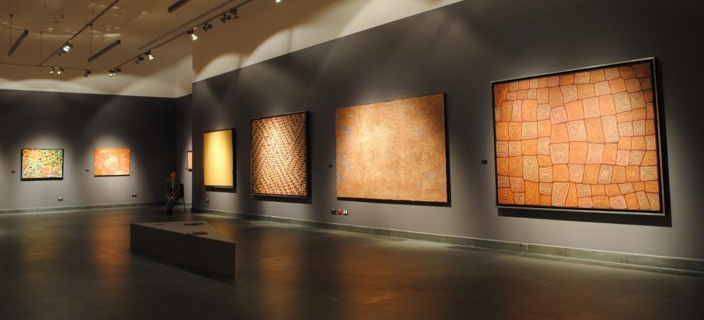 Ujęcie po skosie głównej sali wystawy. Ciemnoszara kolorystyka ścian łącząca się z ciemnoszarym kolorem podłogi potęgują efekt mroczności, przywołując klimat jaskini. Na ścianach wiszą, jeden obok drugiego, dużych rozmiarów obrazy. Punktowe oświetlenie wydobywa geometryczne, abstrakcyjne wzory na płaszczyźnie obrazów, mieniące się ziemistymi kolorami brązów oraz pomarańczy.