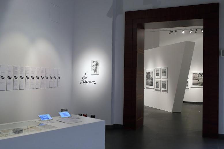 """Z białego przedsionka sali wystawowej, będącego wprowadzeniem do wystawy, otwiera się widok na główną część ekspozycji. Na pierwszym planie, po lewej stronie, wyłania się ustawiona w przedsionku pod kątem prostokątna, biała gablota, przeszklona od góry do połowy swojej długości. Pod szkłem umieszczone są archiwalne dokumenty i listy. Na pozostałej części gabloty stoją małe monitory wyświetlające archiwalne zdjęcia i filmy. Za gablotą, na ścianie od lewej strony, znajdują się prostokątne tablice tworzące graficzną linię czasu z najważniejszymi datami z życia Ernsta Stewnera. Obok wisi oświetlona mocnym światłem punktowym jego niewielka fotografia portretowa z umieszczoną pod nią czarną kaligrafowaną, powiększoną sygnaturą """"Stewner"""", którą fotograf podpisywał swoje zdjęcia. Po prawej stronie fotografii przez otwarte, szerokie i duże przejście wyłania się widok przestrzeni głównej sali wystawowej z ustawioną pośrodku pod kątem białą ścianą ekspozycyjną. Na białych ścianach wiszą czarno-białe fotografie będące współczesnymi odbitkami wykonanymi w oparciu o oryginalne zachowane negatywy. Wszystkie oprawione są w białe ramy."""