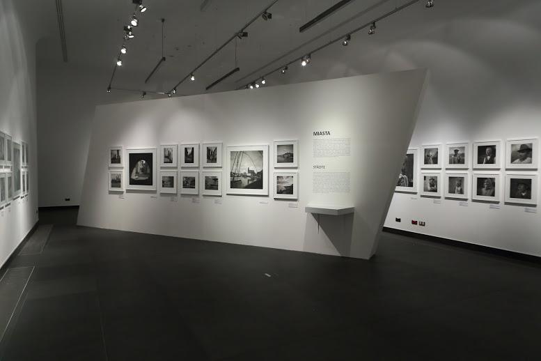 Przestrzeń głównej sali wystawowej. Pośrodku znajduje się wolnostojąca ściana ekspozycyjna ustawiona w poprzek pomieszczenia. Na białych ścianach wiszą czarno-białe fotografie w białych ramach.