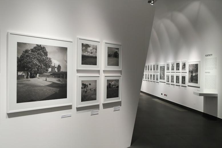 Przestrzeń głównej sali wystawowej przysłania po lewej stronie w dużym zbliżeniu fragment ekspozycyjnej białej ściany. Wisi na niej pięć czarno-białych fotografii w białych ramach. Pierwsza z lewej, duża, przedstawia wiejską scenę z gospodarzem idącym po przydomowym podwórku – tło sceny tworzy korona ogromnego kasztanowca oraz drewniany wiatrak. Cztery mniejsze fotografie zawieszone obok, w kwadracie, jedna nad drugą, prezentują wiejskie krajobrazy oraz ludzi przy pracy na polu podczas sianokosów.