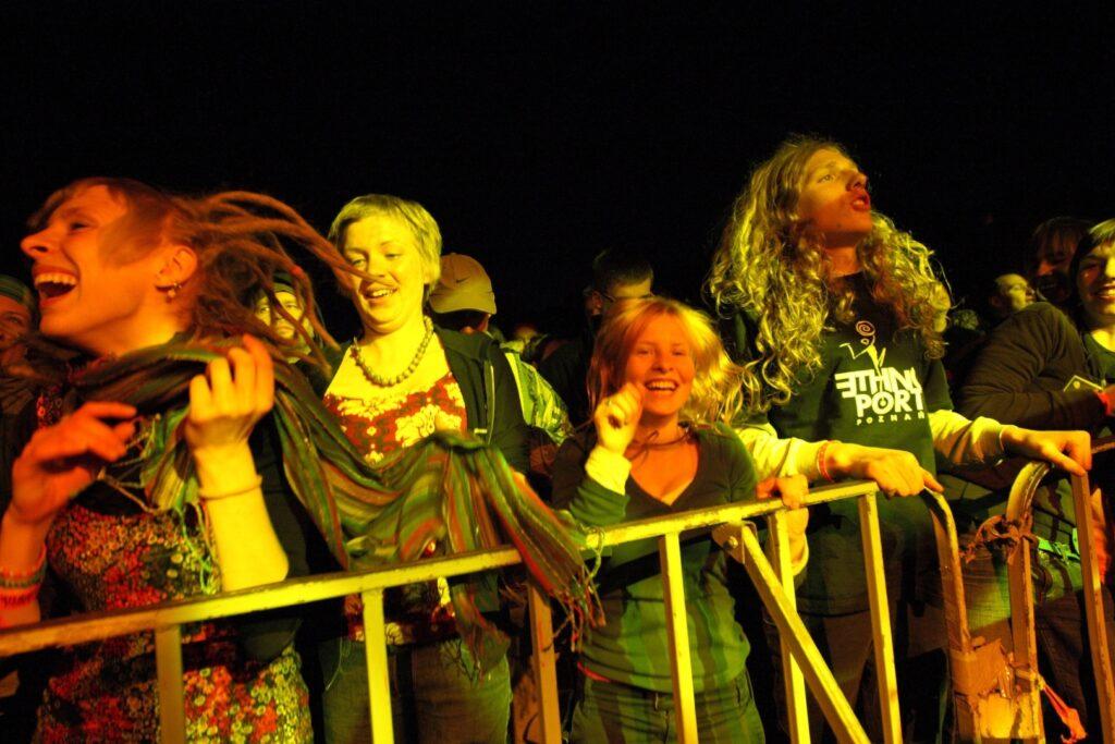 Roztańczeni uczestnicy koncertu bawią się przed barierkami oddzielającymi publiczność od sceny. Na pierwszym planie cztery, roześmiane osoby w tanecznych pozach, oświetlone żółtym światłem bijącym od sceny. W tle widoczne są sylwetki kolejnych bawiących się osób.