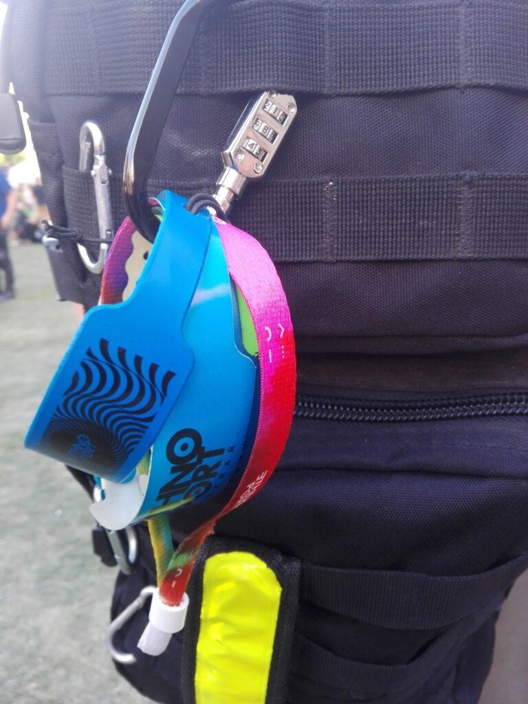 Festiwalowe opaski na plecaku fana (od pierwszej edycji). Bliski kadr ukazuje fragment czarnego plecaka z przypiętymi kolorowymi opaskami festiwalowymi z poprzednich edycji Ethno Portu.