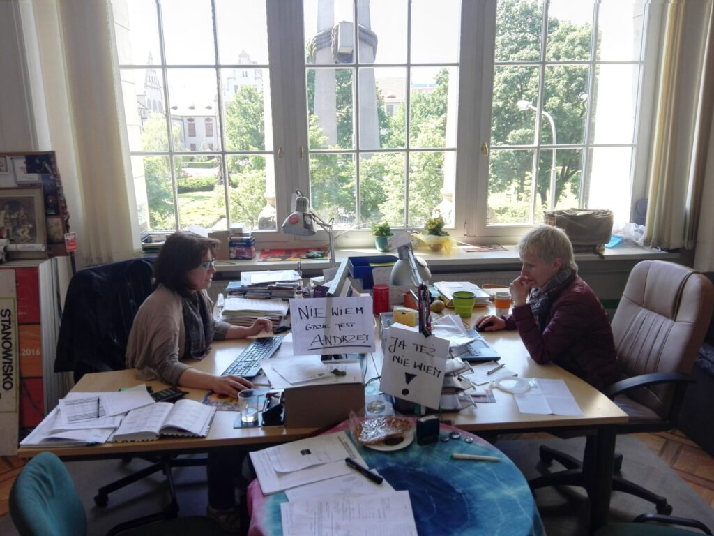 """Biuro festiwalu tuż przed rozpoczęciem kolejnej jego edycji. Przy ustawionych na przeciw siebie biurkach siedzą dwie kobiety, od lewej: Bożena Szota (koordynatorka programu) i Anna Pawłowska (koordynatorka promocji, logistyki i małego ethno). Obie zapatrzone są w monitory swoich komputerów. Na pierwszym planie mały okrągły stolik przykryty kolorowym obrusem. Nad nim widoczne kartki z napisami: """"Nie wiem, gdzie jest Andrzej"""" oraz """"Ja też nie wiem!"""" przypięte do lampek biurkowych. W tle olbrzymie okno, przez które widać krzyże na pl. Adama Mickiewicza i drzewa w parku."""