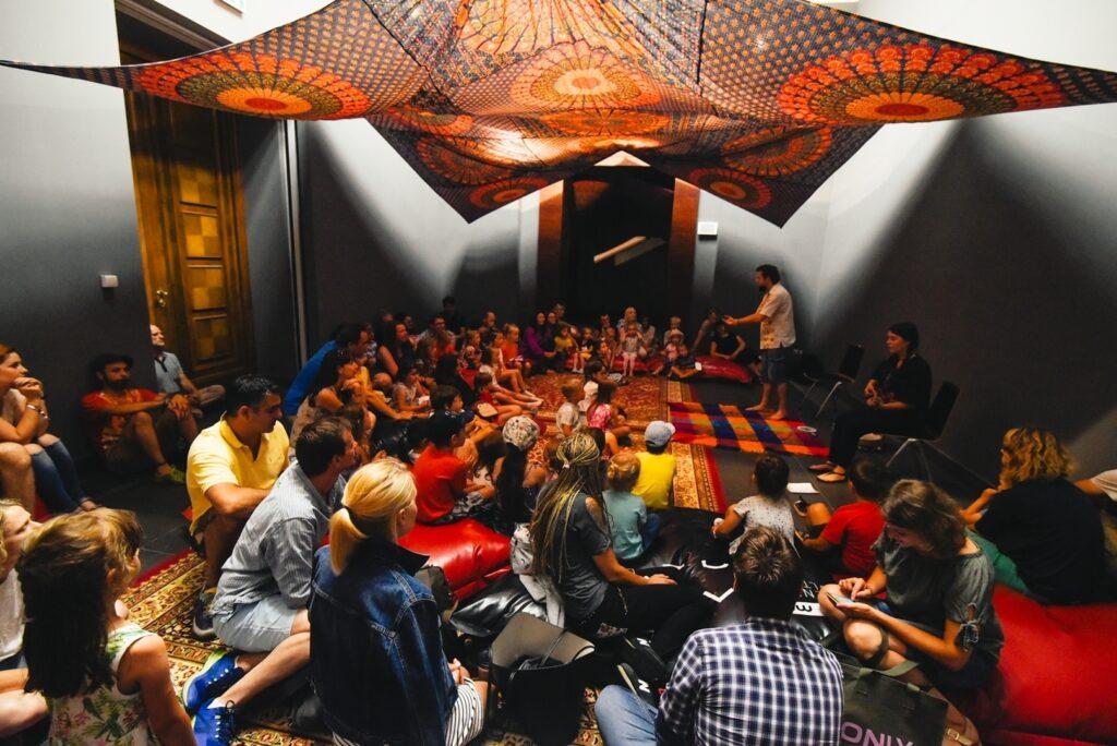 Duża sala o grafitowych ścianach wypełniona jest dziećmi i ich opiekunami. Wszyscy siedzą w półkolu, na dywanach i poduchach. W skupieniu przyglądają się stojącemu pośrodku mężczyźnie, który opowiada baśnie. Pod sufitem zawieszona jest wielka, kolorowa tkanina w etniczne wzory.