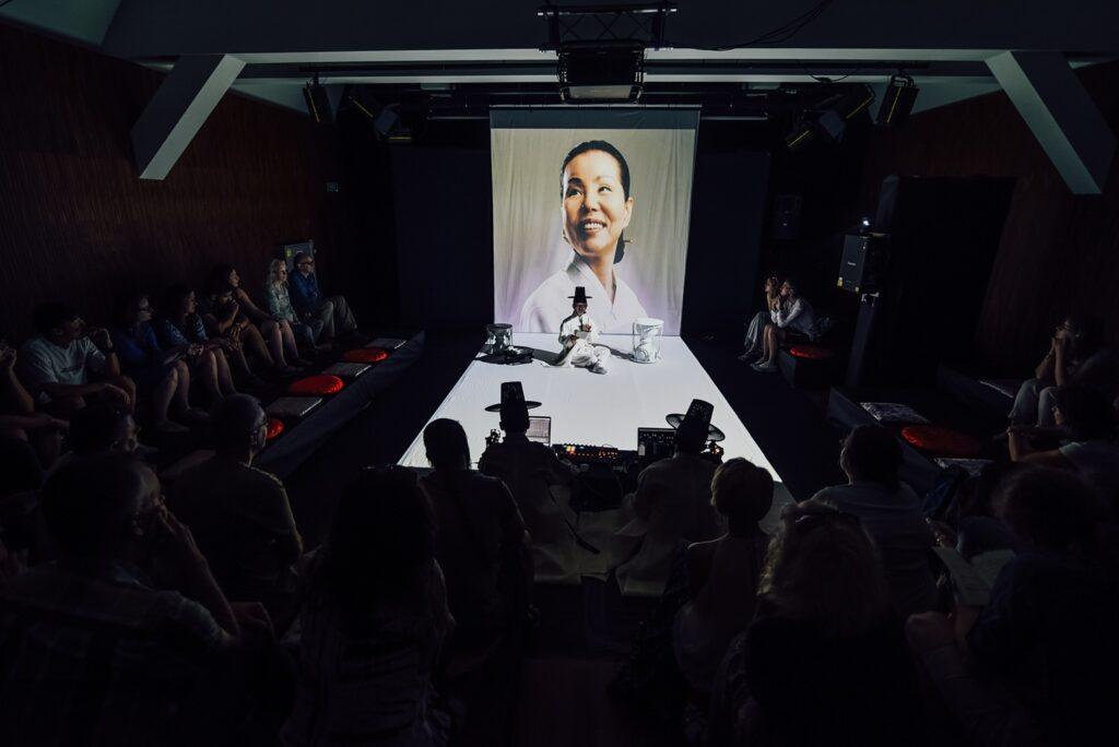 Zdjęcie wykonane zostało podczas kameralnego koncertu w Scenie Nowej. W pomieszczeniu panuje półmrok, jedynie obszar pośrodku kadru jest oświetlony intensywnym, białym światłem. Wyraźnie odcięty idealnie prostymi liniami prostokątny fragment podłogi oraz podobnego kształtu projekcja na tylnej ścianie wyznaczają przestrzeń sceny. Siedzi tam, ze skrzyżowanymi nogami samotna postać. Mężczyzna ubrany jest na biało, na głowie ma czarny, wysoki kapelusz z dość szerokim rondem. Obok niego stoją dwa bębny. Projekcja za jego plecami przedstawia portretową fotografię uśmiechniętej kobiety o rysach twarzy wskazujących na pochodzenie z obszaru południowo-wschodniej Azji. Wokół sceny, na podestach ustawionych w kształt litery U, rysują się szare sylwetki widzów.