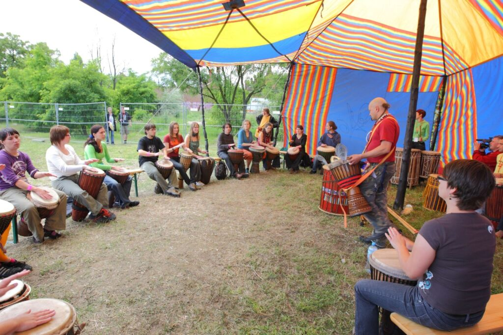 Zdjęcie wykonane na łące w Starym Korycie Warty przedstawia grupę kilkunastu młodych osób siedzących w dużym półkręgu pod kolorowym namiotem. Wszyscy trzymają między kolanami duże afrykańskie bębny w kształcie kielicha oplecionego sznurem – to djembe. Prowadzący stoi przodem do warsztatowiczów, a djembe ma zawieszone na ramieniu na szerokiej taśmie. Uczestnicy są uchwyceni przez fotografującego w momencie wystukiwania dźwięków - mają uniesione dłonie nad swoimi bębnami i uważnie wpatrują się w mistrza. W oddali, po lewej stronie kadru zielona ściana drzew, a po prawej kolejne bębny oraz ekipa telewizyjna z kamerą filmująca zajęcia.