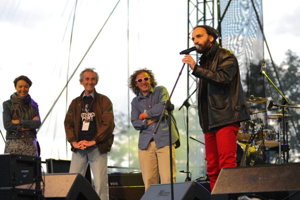 Otwarcie festiwalu w 2009. Kadr z bliska ukazuje cztery osoby stojące na scenie, od lewej: Anna Hryniewiecka (obecna Dyrektorka CK ZAMEK), Marek Raczak (ówczesny Dyrektor CK ZAMEK), Andrzej Maszewski (Dyrektor Festiwalu), Maciej Rychły (festiwalowy konferansjer od pierwszej edycji). Maciej mówi stojąc przy mikrofonie, pozostali przyglądają mu się z szerokimi uśmiechami.