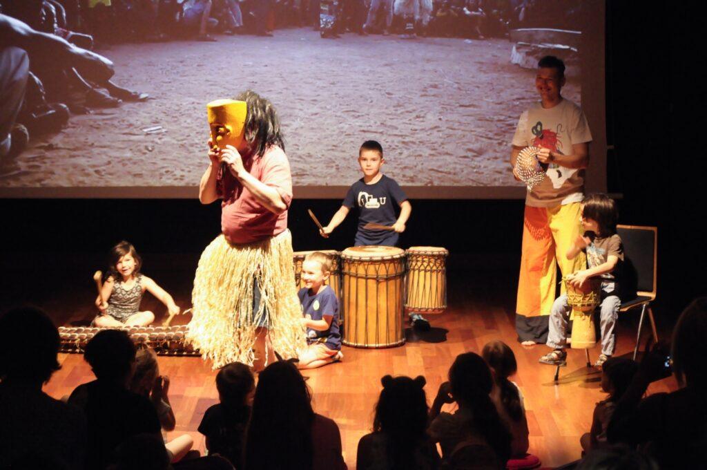 Przed spowitą w ciemnościach publicznością, w jasnej plamie światła rozgrywa się scena spektaklu lub może koncertu. Czworo dzieci i jeden mężczyzna z zapałem grają na etnicznych instrumentach. Przed nimi stoi postać w trawiastej spódnicy trzymająca przed twarzą dużą, żółtą maskę.