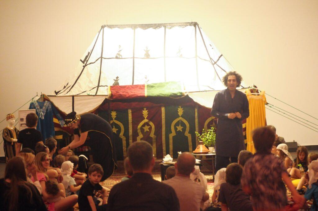 Na tle białej ściany, zalany jasnym światłem stoi zdobny namiot, typowy dla kultury Mahrebu, czyli krajów północno-zachodniej Afryki. Przed nim siedzi na dywanach liczna grupa dzieci i ich opiekunów. Z uwagą słuchają mężczyzny odzianego w długą, granatową tunikę. Na fotografii dostrzec też można detale zdradzające charakter spotkania – stroje, naczynia, produkty spożywcze.