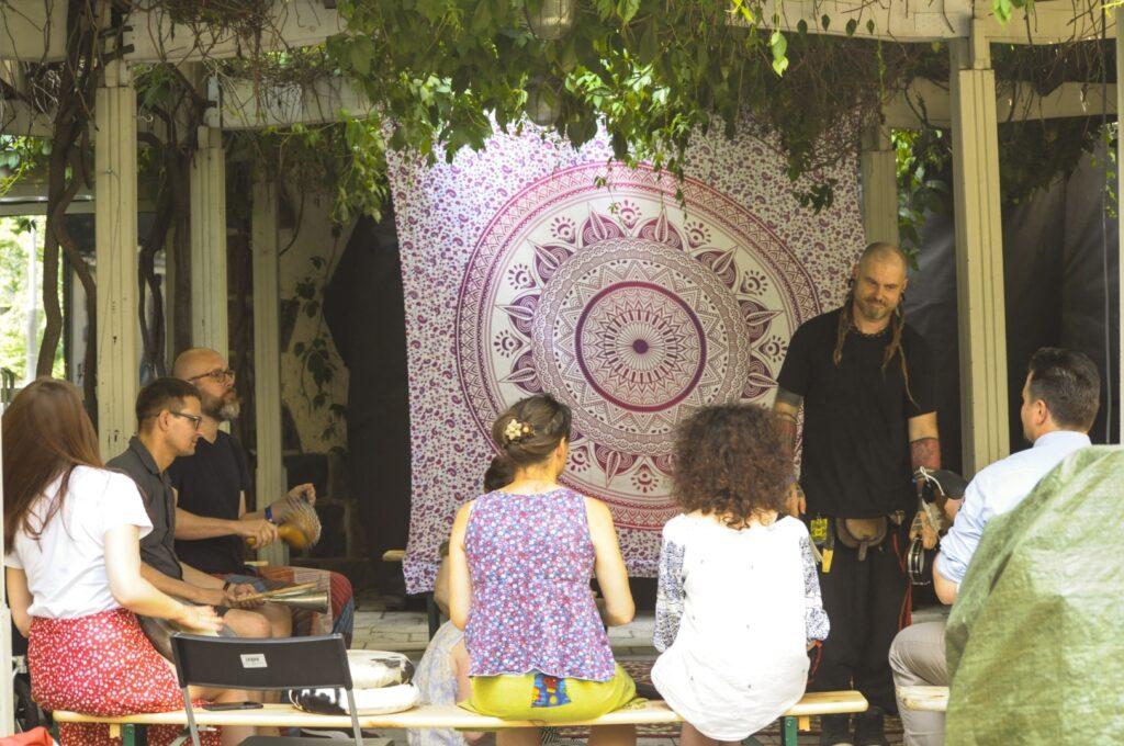 Pod białą pergolą, z której zwisają zielone liście siedzi sześć osób na drewnianych ławkach. Przodem do nich stoi wysoki mężczyzna prowadzący zajęcia. Mężczyzna ma wytatuowane przedramiona i długie dredy z tyłu głowy. Ubrany jest w czarną koszulkę z przypiętym identyfikatorem festiwalowym i luźne spodnie. W tle ma rozwieszoną barwną tkaninę z wzorem indyjskiej mandali. W dłoniach trzyma nieduży tamburyn. Trzech uczestników i trzy uczestniczki wpatrzeni są w prowadzącego, ci ukazani z profilu wyraźnie się uśmiechają, niektórzy trzymają w dłoniach nieduże instrumenty perkusyjne.