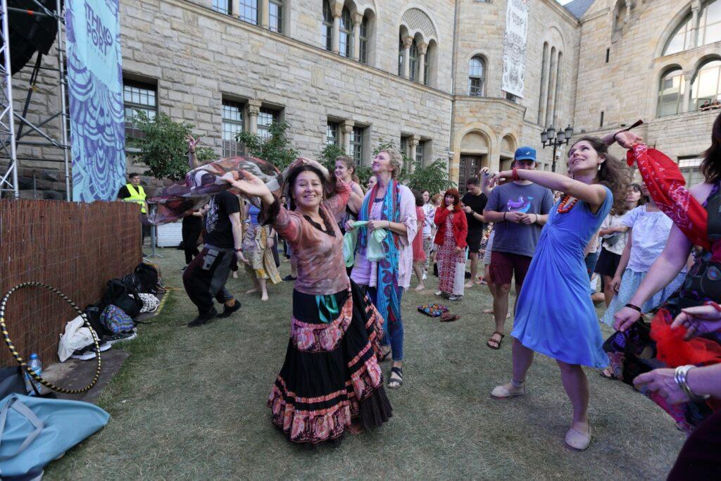 Fotografia przedstawia roztańczoną publiczność na łące przed Zamkiem. Z lewej strony widoczny fragment narożnika sceny. Na pierwszym planie dwie uśmiechnięte, tańczące kobiety z chustami w rękach.