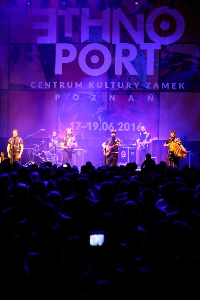 Na pierwszym ciemnym planie publiczność sfotografowana od tyłu, zwrócona w stronę znajdującej się na drugim planie sceny. Głowy słuchaczy oświetlone są delikatnie fioletowym światłem. Na oświetlonej scenie widoczni są muzycy z instrumentami, W tle sceny widoczny jest motyw graficzny z festiwalu w 2016 roku, napis ETHNO PORT Centrum Kultury Zamek Poznań 17-19.06.2016