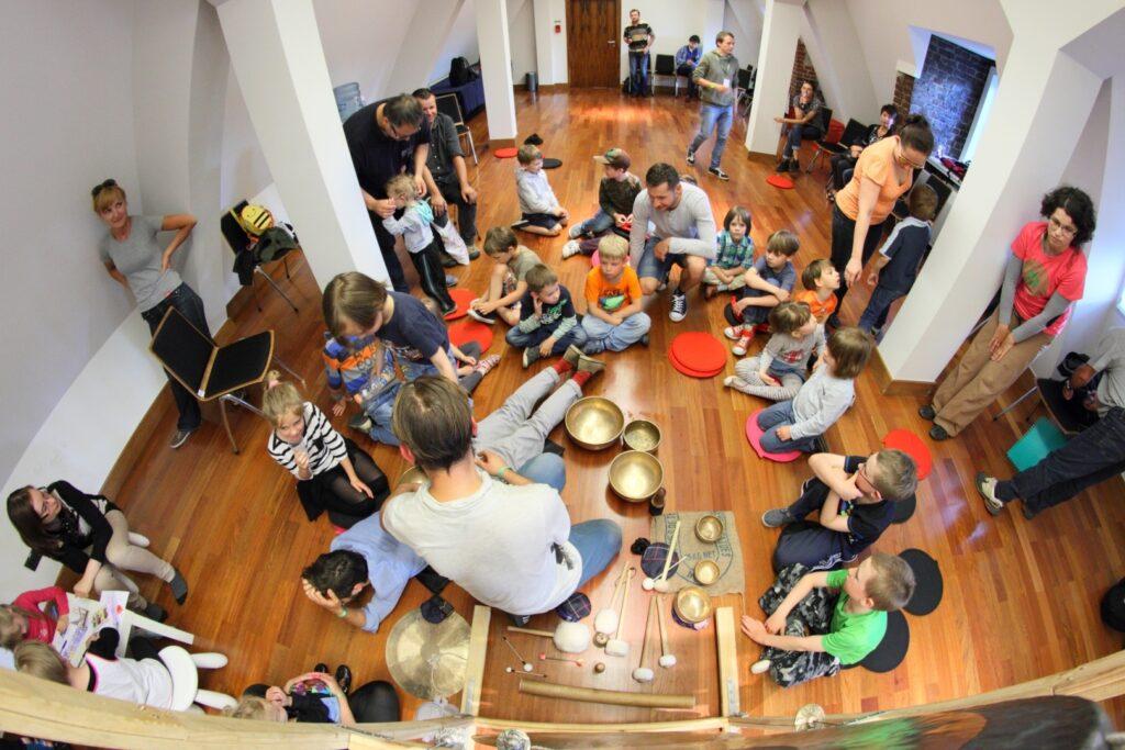 Zdjęcie wykonane jest z góry. Przedstawia liczną grupę dzieci i ich opiekunów siedzących na drewnianej podłodze w jasnej, niedużej sali. Wszyscy zwróceni są w kierunku mężczyzny, wokół którego porozstawiane są różnej wielkości misy tybetańskie oraz pałeczki.