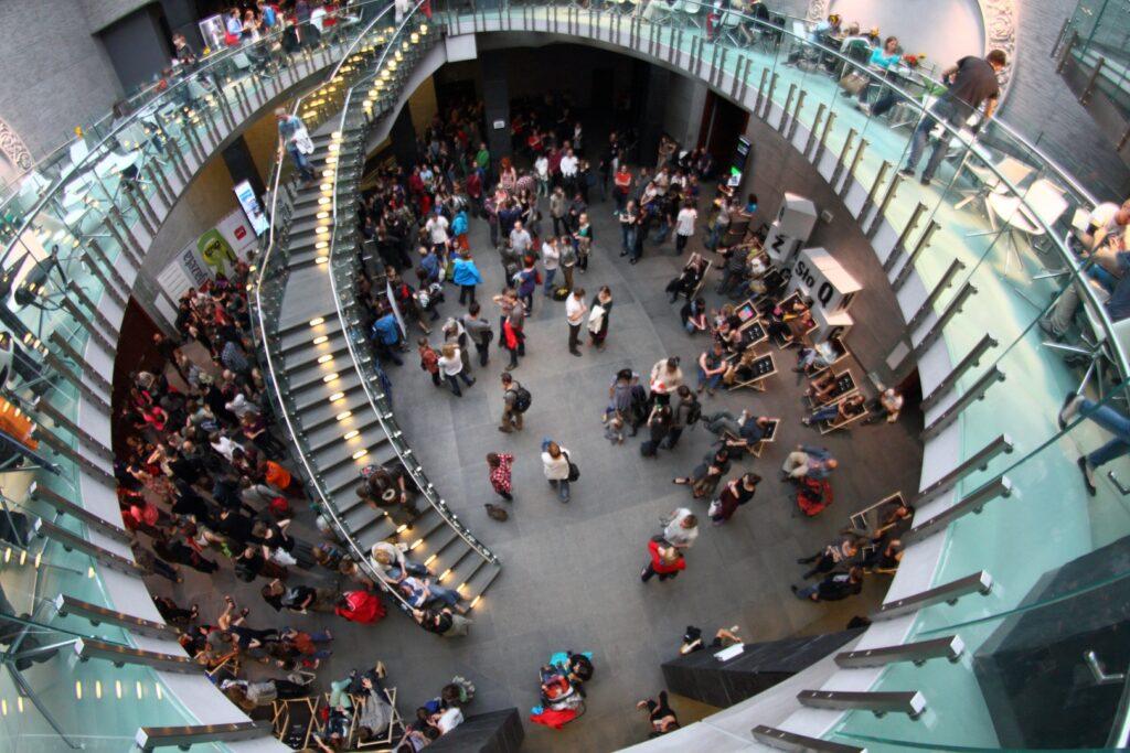 Atrium CK ZAMEK. Zdjęcie wykonane z góry przedstawia stojących tłumnie przed Salą Wielką ludzi. Swoiste obramowanie dla tego kadru stanowi eliptyczna, przeszklona konstrukcja zamkowej kawiarni wraz z lekkimi, półokrągłymi schodami.