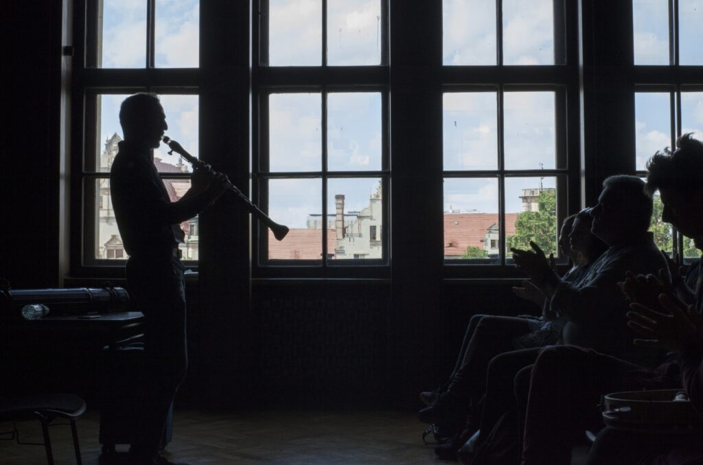 Ciemną salę rozświetlona dzienne światło wpadające przez cztery duże pionowe okna. Z lewej strony fotografii stoi bokiem prowadzący zajęcia i gra na klarnecie. Za nim stolik, na którym leży futerał od instrumentu i butelka wody. Przed nim trochę niewyraźny, zaciemniony pierwszy rząd zasłuchanych uczestników warsztatów. Niektórzy wyklaskują rytm uniesionymi dłońmi. Na kolanach pierwszego uczestnika leży mały tamburyn. Za oknami zielone korony drzew i szczyty zabudowań uniwersyteckich.