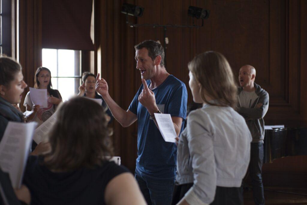W centralnym punkcie stoi mężczyzna o ciemnych włosach w niebieskiej koszulce z uniesionymi w górę palcami wskazującymi obu dłoni. Za nim, po prawej stronie, drugi mężczyzna w szarej bluzie, obydwaj śpiewają w kierunku uczestników. Z lewej strony uczestniczki warsztatów wokalnych, stoją swobodnie w półokręgu i trzymają przed sobą kartki z tekstami pieśni. Śpiewają wraz z prowadzącymi zajęcia. W tle, po prawej, za śpiewającymi niewyraźnie zarysowany fortepian, a nad nimi zawieszone reflektory. Po lewej stronie w tle pionowe okno, przez które wpadają promienie słoneczne.