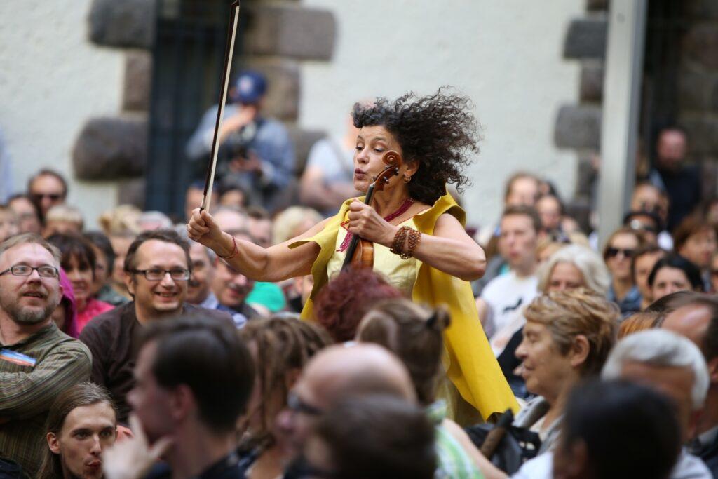 Jasna fotografia wykonana na Dziedzińcu Zamkowym przedstawia jedną z artystek biegnącą między siedzącymi na widowni ludźmi. Iva Bittová zdaje się frunąć wśród publiczności. Ubrana jest w żółtą sukienkę i kamizelkę. Jej ciemne włosy powiewają na wietrze. W lewej dłoni trzyma skrzypce, a w prawej smyczek. Wokół siedzą zaskoczeni, uśmiechnięci uczestnicy koncertu.