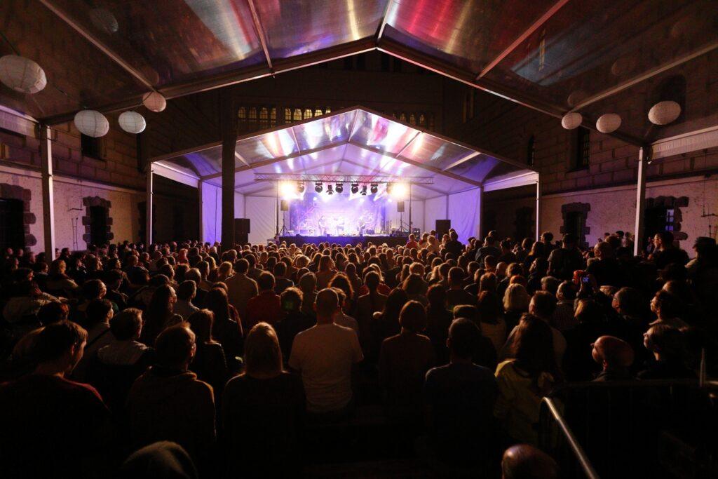 Namiot na Dziedzińcu Zamkowym. Zdjęcie wykonane zostało podczas nocnego koncertu. Fotograf stał za publicznością, kierując oko obiektywu na rozświetloną scenę. Większą część kadru wypełniają ciemne sylwetki tłumnie zebranych na dziedzińcu słuchaczy. Ich głowy muśnięte są jasnym, ciepłym światłem bijącym od sceny. Skąpane w blasku reflektorów postacie artystów są słabo widoczne. Nad sceną i widownią rozpięty jest przezroczysty dach, na którym odbijają się wielobarwne światła.