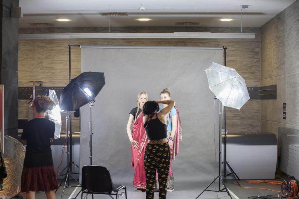 """Zdjęcie zostało wykonane podczas realizacji """"Garderoby świata"""", jednego z elementów programu """"Wszyscy jesteśmy migrantami"""", w 2016 roku. Przedstawia atelier fotograficzne zaaranżowane w Holu Głównym CK ZAMEK. Największy obiektem na zdjęciu jest jasny ekran służący za tło dla pozujących osób. Dwie młode dziewczyny o blond włosach, ubrane w hinduskie sari, czekają na wykonanie pamiątkowej fotografii. Robiąca zdjęcie kobieta stoi przed nimi, odwrócona do nas tyłem. Na lewo od niej stoi czarne krzesło, a dalej, również odwrócona tyłem, dziewczyna. Najbardziej charakterystycznymi przedmiotami na obrazie są ustawione z obu stron ekranu parasole umieszczone na czarnych metalowych stojakach. Prawy jest jasny, a lewy ciemny. Spod obydwu wydobywa się światło lamp, gwarantujących profesjonalną jakość wykonywanej fotografii."""