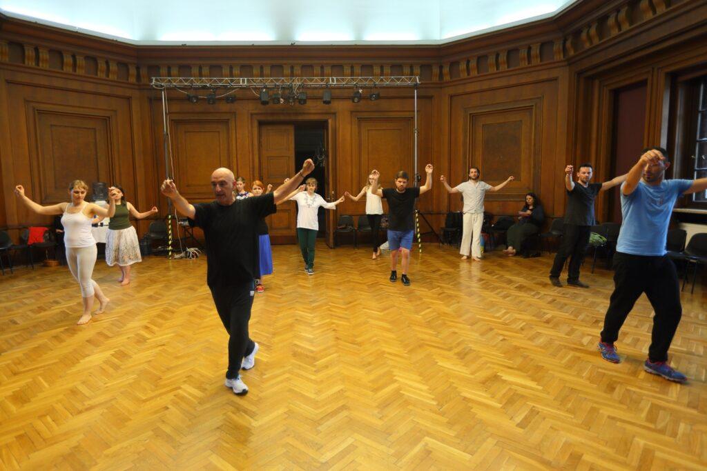 Zdjęcie wykonane w sali o ciemnych, wyłożonych drewnianą boazerią ścianach i z jasnym parkietem. Dwóch prowadzących warsztaty taneczne prezentuje układy nóg z uniesionymi w górze rękoma, w charakterystycznym galicyjskim tańcu. Za nimi grupa uczestników, w podobnych pozach wykonuje pierwsze taneczne układy. Wszyscy swobodnie ubrani, w dużych odstępach od siebie. Niektórzy uczestnicy mają bose stopy, Wzdłuż ścian ustawione są ciemne krzesła, na których rozłożone są gdzieniegdzie przedmioty należące do tańczących. Po prawej stronie siedzi na krześle ciemnowłosa dziewczyna. W tle za tańczącymi drzwi wejściowe do sali, a nad nimi rampa z reflektorami scenicznymi.