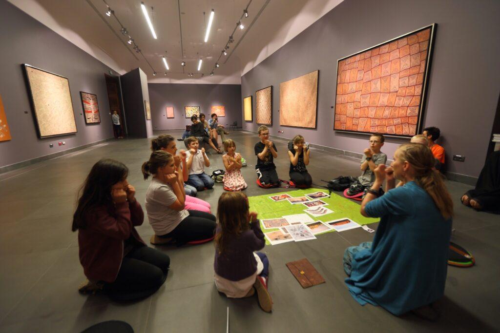 Pośrodku wielkiej sali wystawienniczej, na szarej posadzce siedzi grupa dzieci i jasnowłosa kobieta. Pomiędzy nimi, na zielonej tkaninie leżą barwne kartki. Popielate ściany pomieszczenia zdobią wielkoformatowe obrazy przedstawiające malarstwo aborygeńskie.