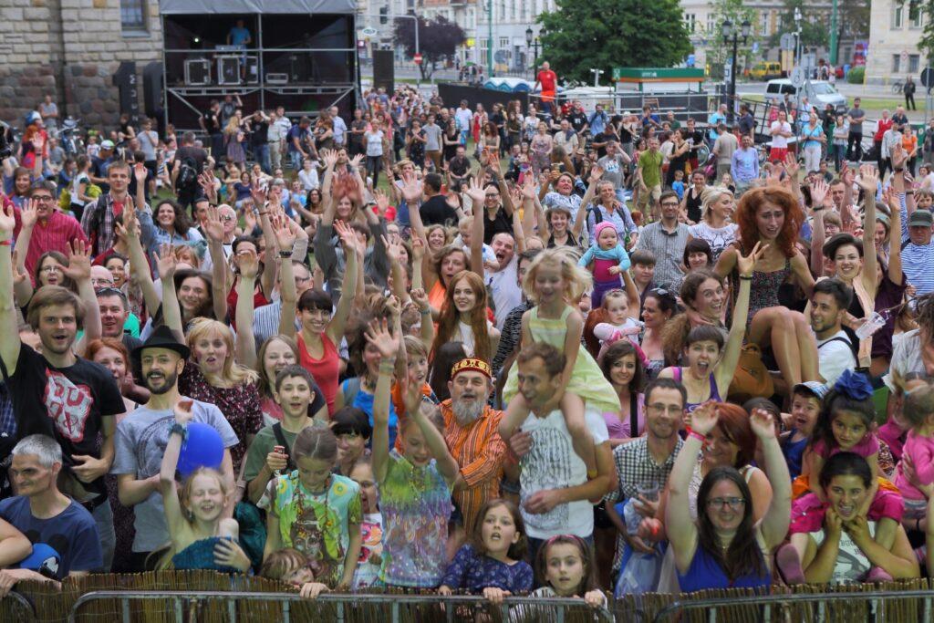 Roześmiany, kolorowy tłum w czasie koncertu przed Zamkiem. Zdjęcie wykonane zostało ze sceny w kierunku widowni. Radośni ludzie z rękoma w górze pozują do wspólnego zdjęcia. W tle widoczne są elementy infrastruktury festiwalowej - realizatorka i podest dla osób z niepełnosprawnościami oraz fragment skrzyżowania ulicy Święty Marcin i Kościuszki.