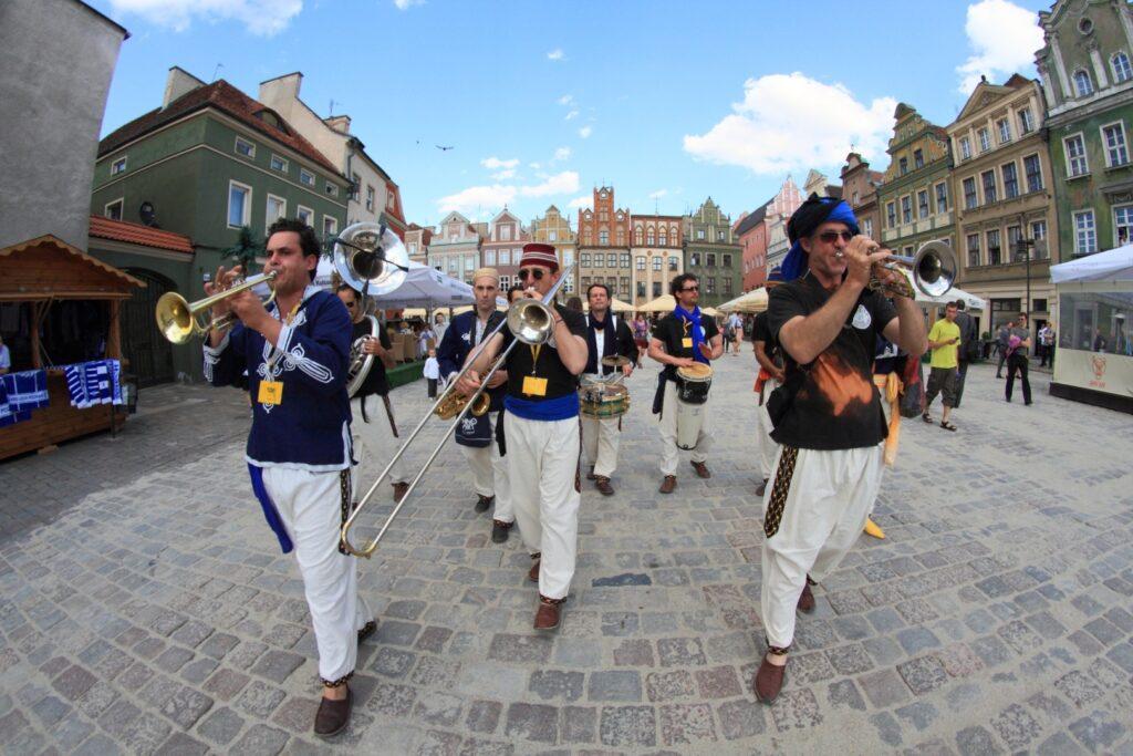 Po płycie poznańskiego Starego Rynku, wśród kolorowych kamieniczek maszeruje kilku, czy nawet kilkunastoosobowa orkiestra. Na przodzie puzonista i dwaj trębacze. Za nimi widać fragmenty innych instrumentów dętych a także perkusyjnych. Wszyscy muzycy ubrani są w stroje stylizowane na tradycyjne ubiory z Algierii. Nad ich głowami rozciąga się błękitne niebo.