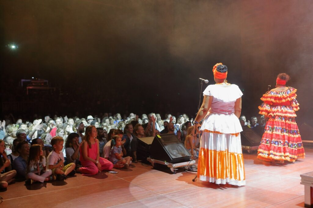 Zdjęcie wykonane zostało ze sceny. Na pierwszym planie, po prawej, tyłem do obiektywu, stoją przy mikrofonach dwie wokalistki. Obie kobiety ubrane są długie, falbaniaste, barwne suknie rodem z Ameryki Południowej. Na strojach dominują: pomarańcz, czerwień i biel. Ciemne, upięte wysoko włosy artystek przepasane są pomarańczową tkaniną. Na dalszym planie znajduje się tłumnie zebrana w Sali Wielkiej publiczność. Głowy stojących najbliżej sceny uczestników koncertu zalewa jasne, białe światło. Pozostali giną w półmroku sali. Na skraju sceny siedzi kilkoro dzieci.