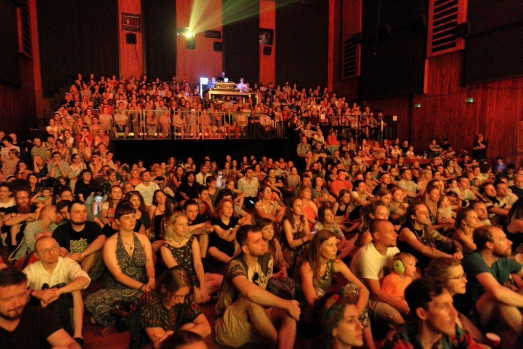 Sala Wielka CK ZAMEK szczelnie wypełniona publicznością. Zdjęcie wykonane jest spod sceny w kierunku widowni. Zasłuchany tłum z uwagą wpatruje się w scenę. Osoby na pierwszym planie siedzą na podłodze, z tyłu kolejni uczestnicy zajmują miejsca na amfiteatralnej widowni. Wszyscy oświetleni są równomiernym, delikatnym, pomarańczowym światłem. Z umieszczonego w tylnej ścianie sali projektora wydobywa się jasna wiązka światła.