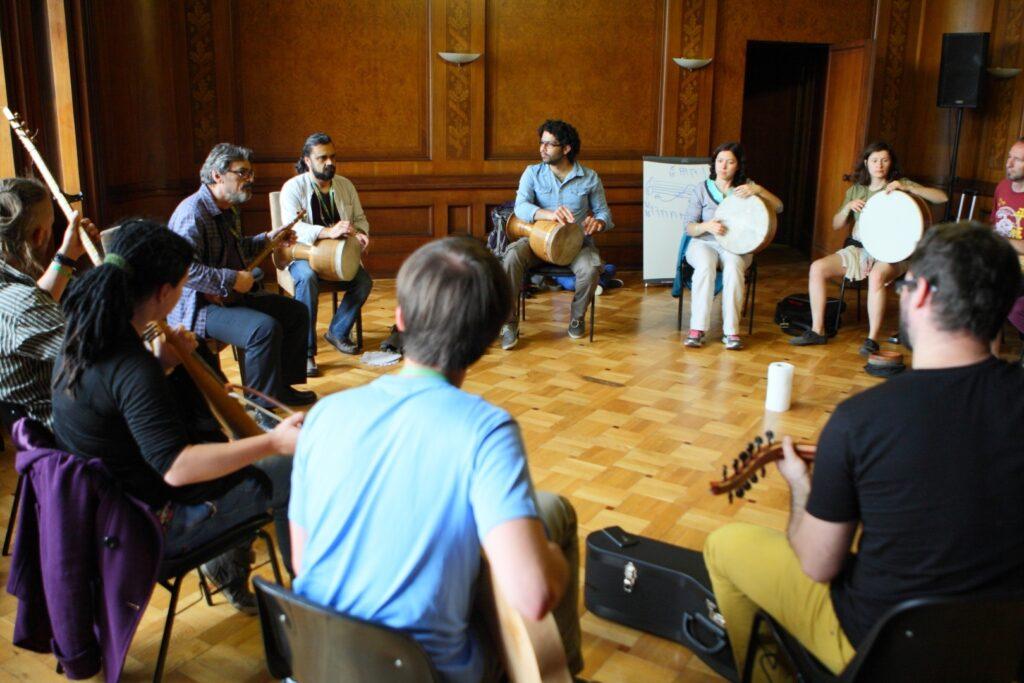 Zdjęcie przedstawia uczestników i prowadzących warsztaty siedzących w kręgu na czarnych krzesłach. Zwróceni twarzami do siebie, w skupieniu trzymają na kolanach różne instrumenty strunowe i perkusyjne. Dwaj mistrzowie siedzą po lewej stronie. To ciemnowłosi, dojrzali mężczyźni z czarnym zarostem, prezentujący uczestnikom oryginalne tradycyjne instrumenty pochodzące z Iranu – strunowy tar i bęben o nazwie tombak. Pomiędzy krzesłami leżą futerały na instrumenty, a z tyłu sali przy drzwiach stoi tablica z niewyraźnymi zapiskami.