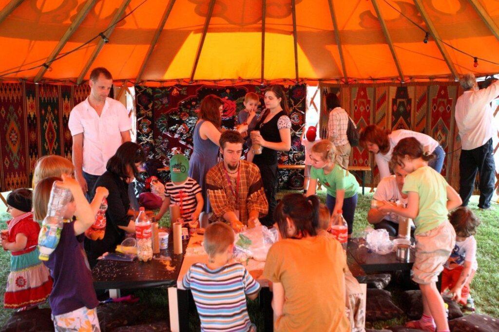 Na fotografii uwiecznione zostały warsztaty budowania etnicznych instrumentów muzycznych. Uczestnicy znajdują się we wnętrzu wielkiej, barwnej jurty. Niektórzy stoją, inni siedzą na rozłożonych na trawie poduszkach. Fotografia jest niezwykle kolorowa i pełna ruchu.
