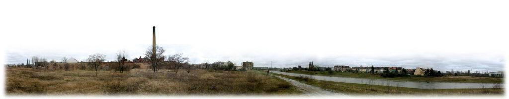 Na panoramicznym zdjęciu widoczny jest teren starego koryta Warty, w którym przez pierwszych kilka lat odbywał się Ethno Port. Od lewej widoczne są dzikie łąki, w tle zabudowania gazowni, gruntowa droga na wale przeciwpowodziowym, rzeka Warta, a za nią majaczy w oddali Katedra i zabudowania Ostrowa Tumskiego. Nad wszystkim góruje zasnute białymi chmurami niebo.