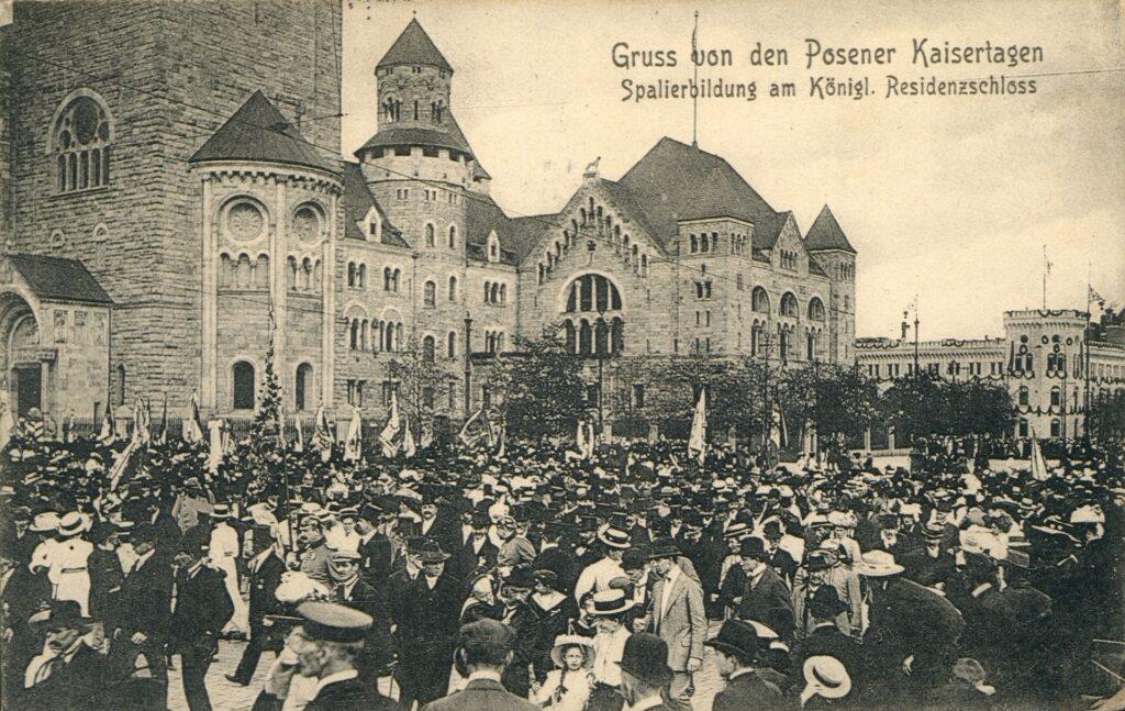 Pocztówka przedstawia tłum przed Zamkiem zgromadzony w tym miejscu z okazji tak zwanych Dni Cesarskich. W tle widoczna jest znaczna część elewacji Zamku oraz fragment budynku Intendentury. Odświętnie ubrani ludzie formują szpaler. Można domniemywać, że okazją do zgromadzenia był przyjazd samego Wilhelma II.