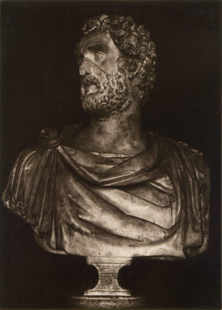 Zdjęcie przedstawia kamienne popiersie mężczyzny o kędzierzawych włosach i brodzie, z udrapowaną na ramionach szatą. Głowę skierowaną ma w lewą stronę.